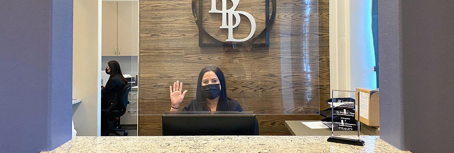 A team member at front desk waving