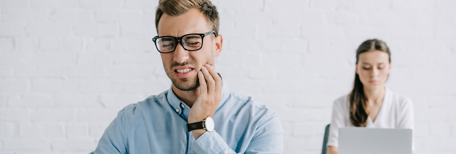 Young businessman in eyeglasses suffering from tooth pain